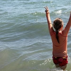 young girl in the sea water with two arms up