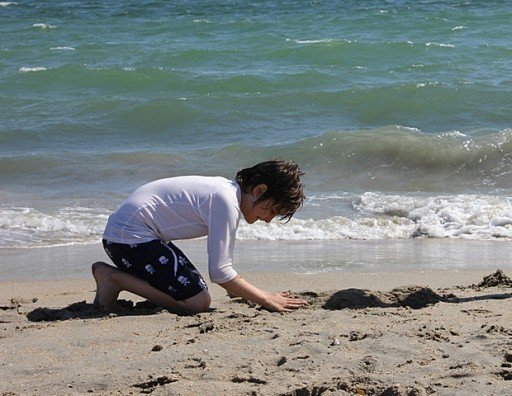 young boy playing in the sand near the sea water