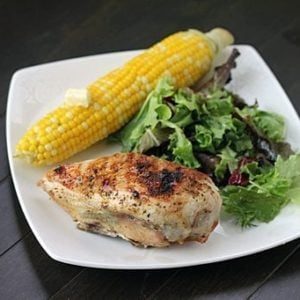 BBQ chicken breast in white plate with vegetable salad and corn in cob