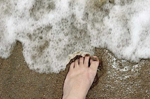 foot in the sand with sandal tan lines