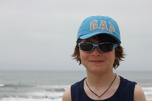 close up of young boy wearing blue cap and sun glasses
