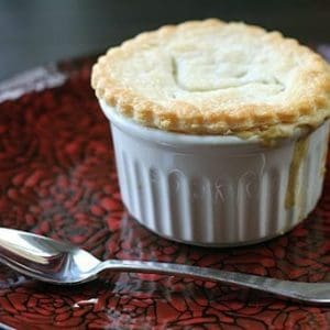 Mini Chicken Pot Pies in white ramekins on a red rose designed plate with spoon