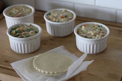 4 white ramekins filled with cooked chicken and vegetable soup, 4 pieces of cut out pie to cover each ramekins