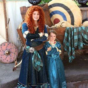 young girl wearing princess Merida dress and the Disneyland character princess Merida
