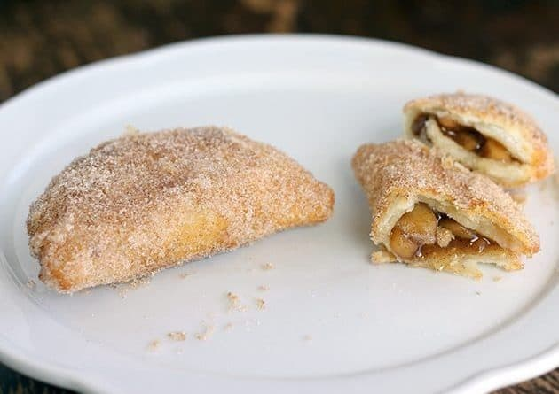 Mini Apple Fried Pies in white plate, one pie broke into half showing the filling inside it