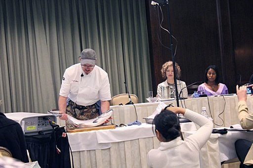 chef holding a big fish in the set up table while participants are watching him