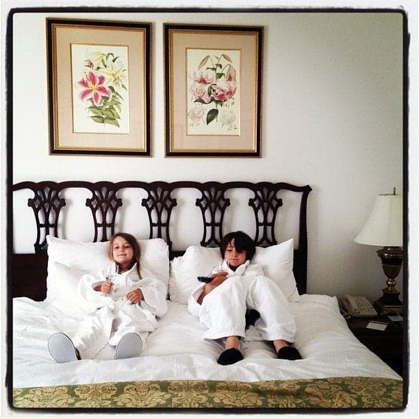 two kids in the king size bed, wearing white robes and holding wine glasses