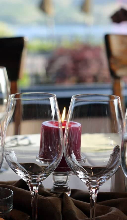 close up of wine glasses and red lighted candles