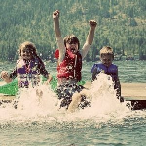 three kids wearing life jackets, sitting down on a dock enjoying splashing water using their feet
