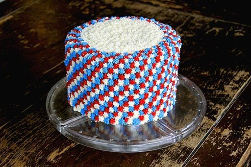 clear cake holder with Fourth of July cake with white, blue and red icing all over