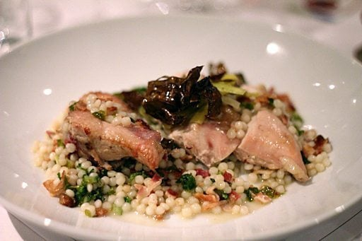 a plate of apple wood smoked chicken supreme with bacon lardons, sautéed kale and Israeli couscous