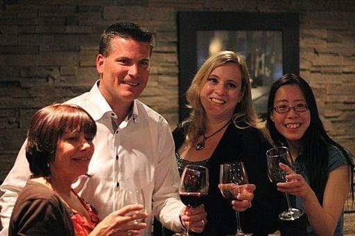Edmonton oiler with three ladies holding glasses of wine