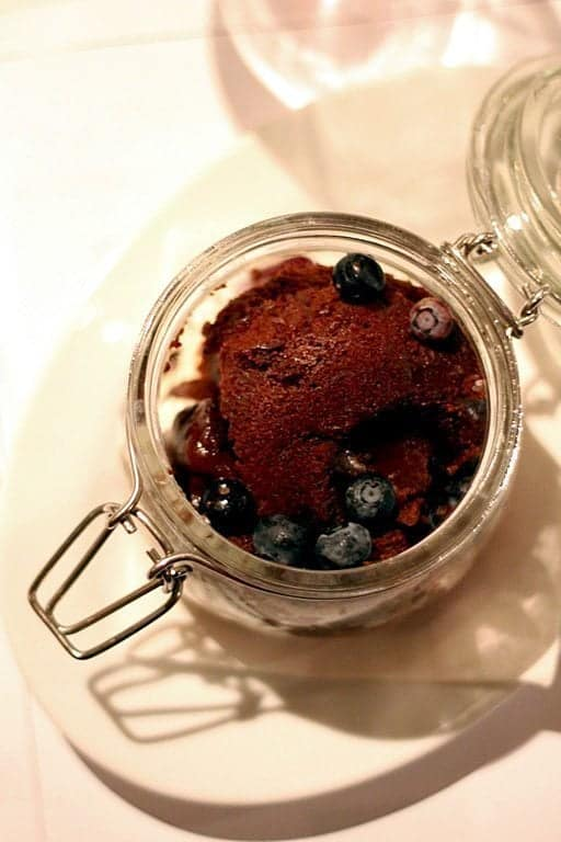 top down shot of chocolate lava cake with grand marnier raspberry coulis and butterscotch gelato in a jar