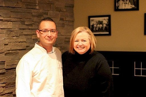 a chef in white uniform together with a Food Blogger wearing black