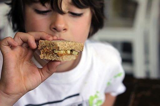 little boy having a bite of sweet peanut butter and pickle sandwich