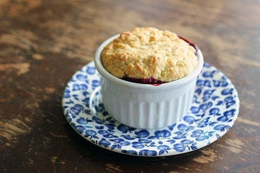 Old Fashioned Saskatoon Cobbler in a white ramekins with biscuit topping placed on a blue saucer plate