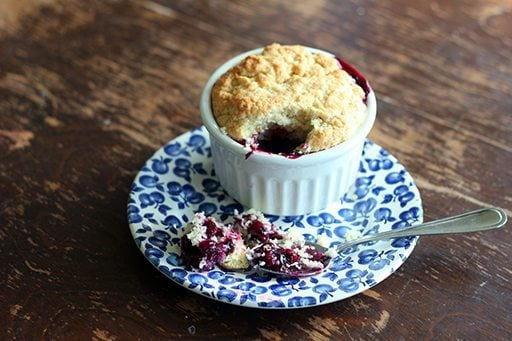 a spoon of rich Saskatoon berry filling with the cakey biscuit topping on blue saucer plate beside white ramekins
