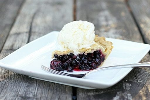 a slice of saskatoon pie topped with vanilla ice cream in a white plate on wood background