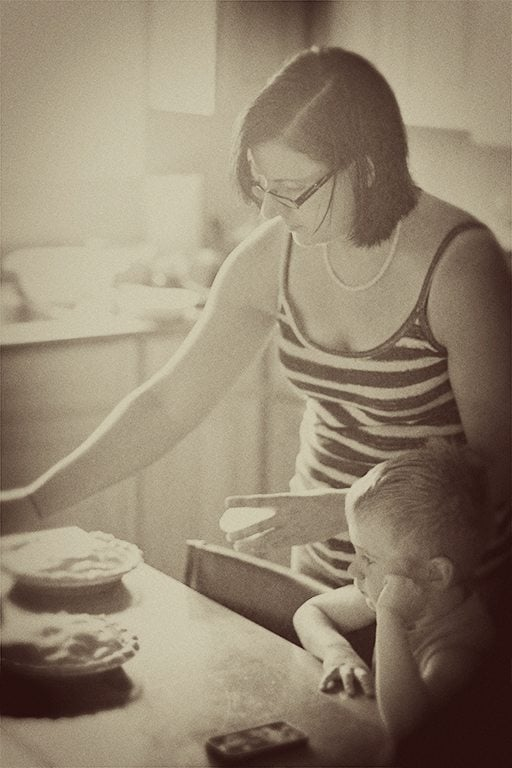 vintage photo of mother preparing saskatoon pie with her son on her side