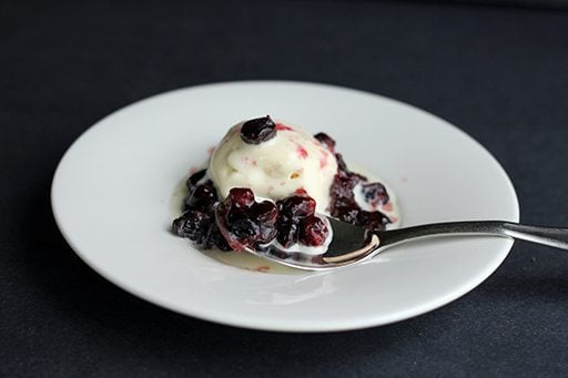 Saskatoon Berry Sauce in a white plate, topped with vanilla ice cream