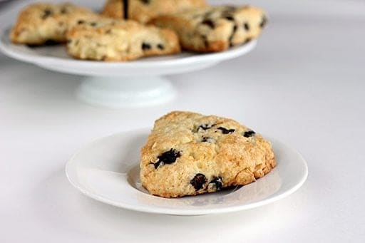 close up slices of White Chocolate Saskatoon Berry Scones in white plate and in cake holder