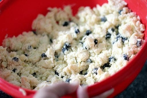 all ingredients for White Chocolate Saskatoon Berry Scones whisked together in a large red bowl