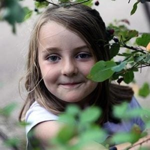 close up of little girl in Saskatoons tree