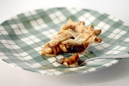 a slice of Amaretto Raisin Crabapple Pie in a checkered green plate with a spoon