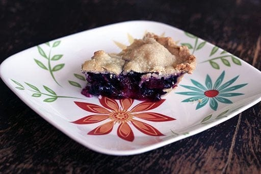 close up slice of Blueberry Rhubarb Pie in a white plate with floral design
