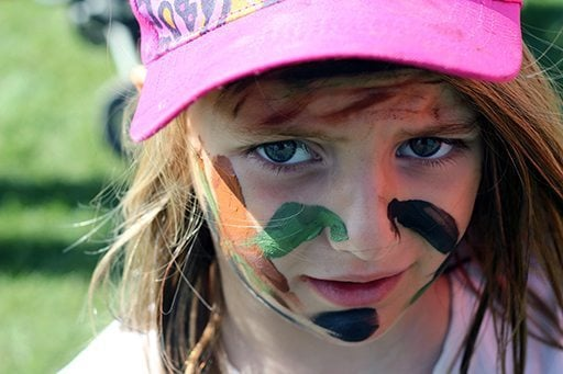 close up little girl with camo painted face