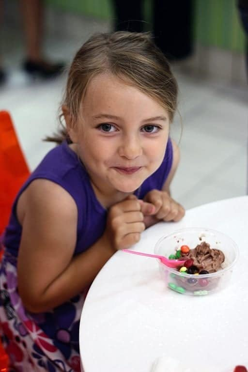 a cup of frozen yogurt with chocolate candies in front of a little girl