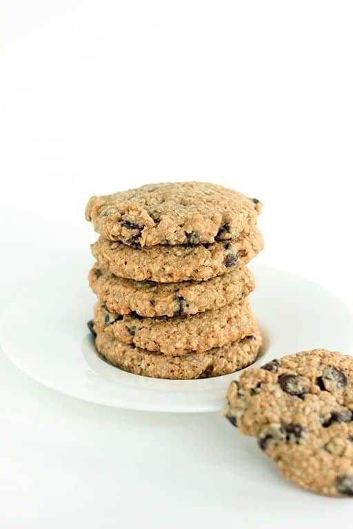 stack of whole wheat oatmeal cookies in a white plate on white background