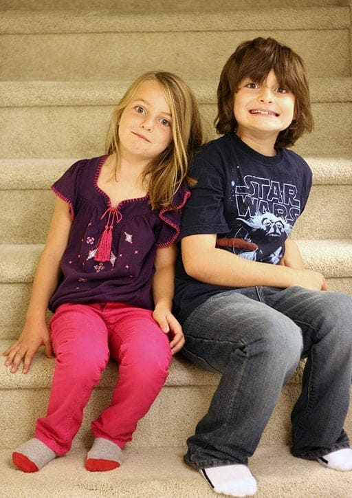 young girl and boy siblings sitting in the stairs