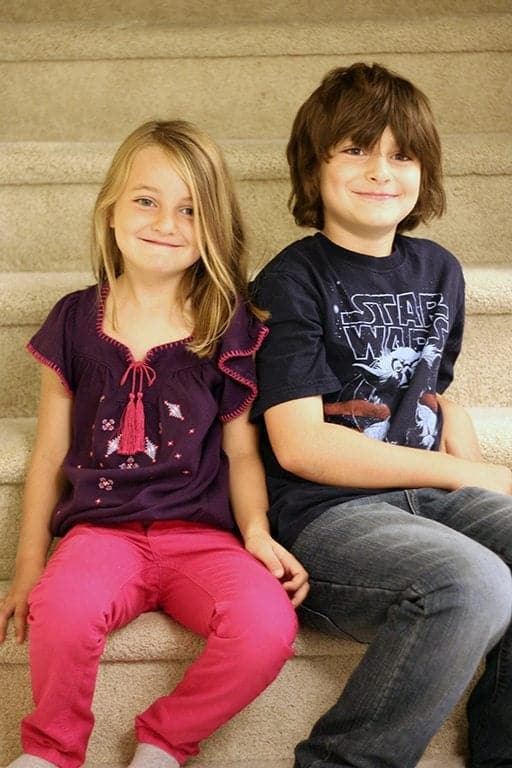 close up of young girl and boy sibling sitting in the stairs