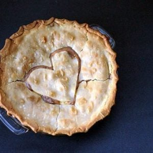 Peaches & Cream Pie in a pie dish with heart shape on top crust