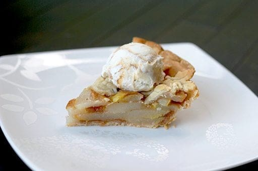 close up slice of Pear Pie in a white plate topped with a scoop of ice cream