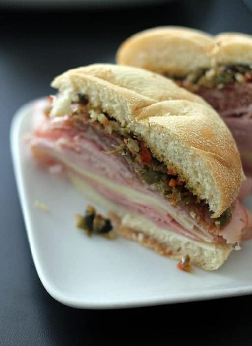 close up of muffalatta sandwich in white plate