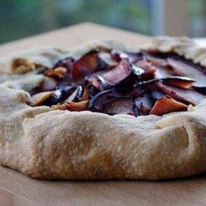 Plum Crostada with cornmeal crust on a wooden background