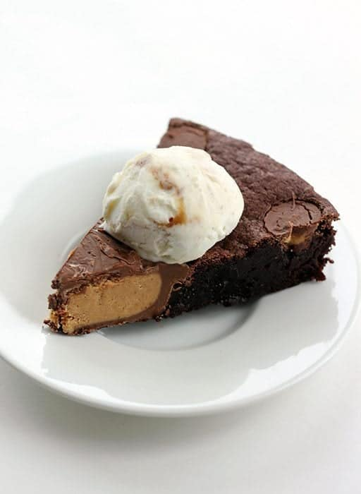 a slice of Giant Reese's PB Cup Skillet Brownie topped with a scoop of vanilla ice cream
