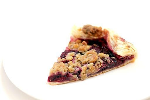 slice of raspberry galette with walnut struesel topping in a white plate