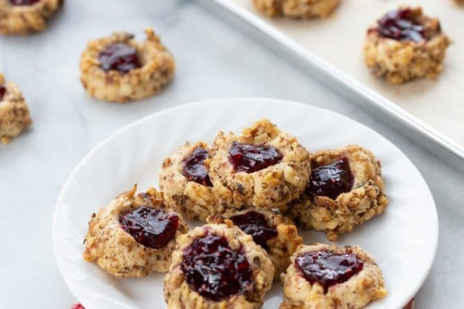freshly baked Raspberry Walnut Thumbprint Cookies in a white plate and in parchment lined baking sheets