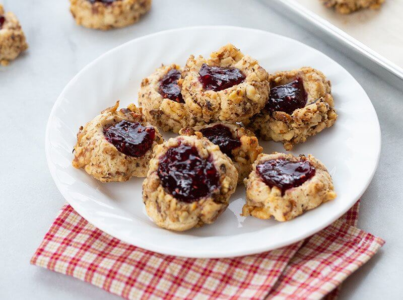 Raspberry Walnut Thumbprint Cookies in a white plate with red checkered cloth underneath