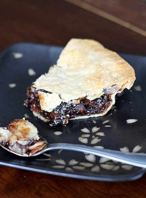 close up of a slice of mincemeat pie in a black plate with a spoon