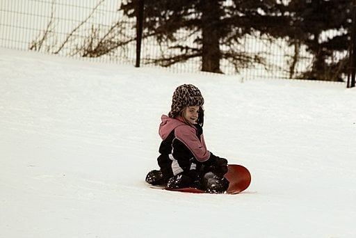 young girl in red sled started to slide in the snow