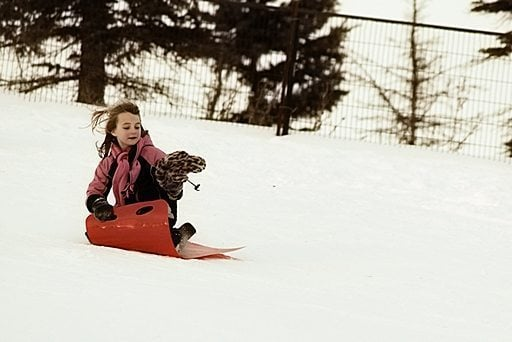 young girl holding her winter hat while in the red sled