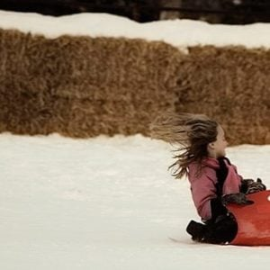young girl enjoys sledding over snow on a sled