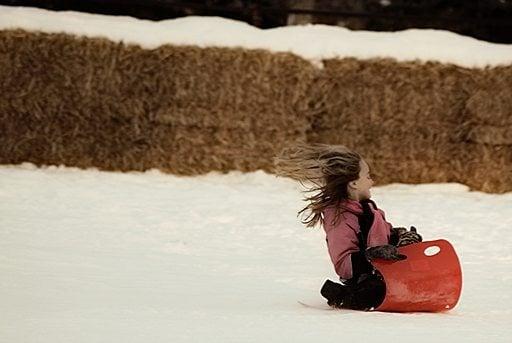 young girl enjoys sledding over snow on a sled