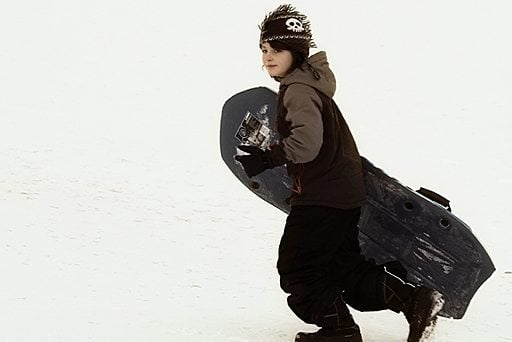 young boy walking in the snow with his sled