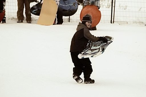 young boy setting up his sled in the snow