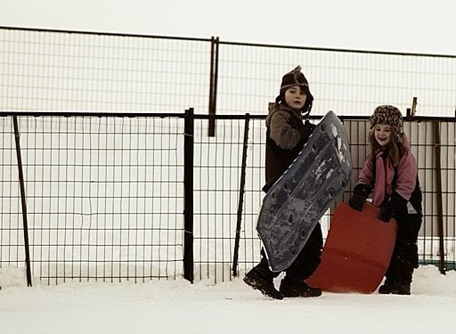 two kids standing in the snow with their sleds